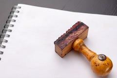 Viejo sello de goma de madera en un pedazo blanco de cuaderno Accesorios de la oficina en una tabla imagen de archivo