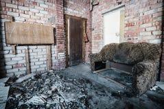 Viejo sitio espeluznante abandonado de la casa señorial y un sofá en él Fotografía de archivo libre de regalías