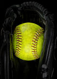 Viejo softball en un guante Imagenes de archivo