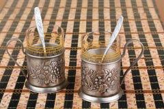 Viejo soporte de vaso del metal dos adornado con un bajorrelieve Foto de archivo