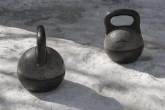 Viejo soporte pesado negro del kettlebell dos en la nieve Imagen de archivo