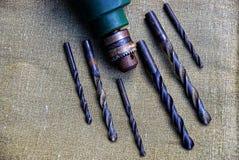 Viejo taladro eléctrico y taladros oxidados en el paño Foto de archivo libre de regalías