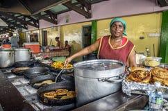 Viejo vendedor de comida del mercado que cocina en Curaçao Foto de archivo