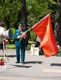 Viejo veterano con la bandera roja el día de la victoria Foto de archivo