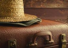Viejo vintage, maleta retra y sombrero de paja en fondo oscuro Concepto del viaje, entonado Fotos de archivo libres de regalías
