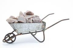 Viejo weelbarrow con las rocas adentro Imagenes de archivo