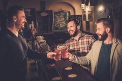 Viejos amigos que beben la cerveza de barril en el contador de la barra en pub Fotos de archivo