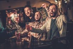 Viejos amigos que se divierten que mira un partido de fútbol en la TV y que bebe la cerveza de barril en el contador de la barra