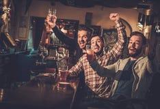 Viejos amigos que se divierten que mira un partido de fútbol en la TV y que bebe la cerveza de barril en el contador de la barra  Fotos de archivo libres de regalías