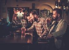 Viejos amigos que se divierten y que beben la cerveza de barril en el contador de la barra en pub imagen de archivo