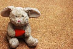 Viejos descensos de la muñeca del conejo en la tierra marrón Imagenes de archivo