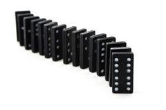 Viejos dominós negros en fila aislados en un fondo blanco foto de archivo