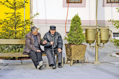 Viejos hombres que se sientan en un banco de parque en Bitola fotos de archivo libres de regalías