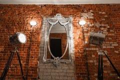 Viejos marcos adornados en los glas del espejo que cuelgan una pared de ladrillo Fotos de archivo libres de regalías