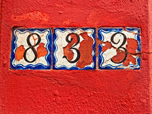 Viejos números en una pared roja Imagen de archivo libre de regalías