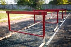 Viejos obstáculos rojos para una carrera de vallas en estadio abandonado Fotografía de archivo