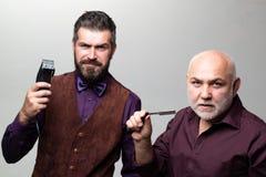 Viejos padre e hijo - concepto de la barbería Día de padres Peluquero que visita del hombre mayor en barbería fotografía de archivo