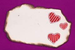 Viejos papel y corazones quemados en blanco Imagen de archivo libre de regalías