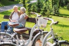 Viejos pares cariñosos que se relajan después de completar un ciclo Fotografía de archivo