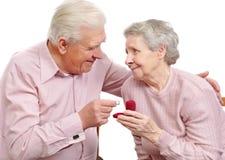 Viejos pares felices con el anillo de compromiso en forma de corazón Imagen de archivo libre de regalías