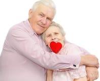 Viejos pares felices con el caramelo rojo Imágenes de archivo libres de regalías