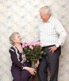Viejos pares felices y ramo grande de rosas rosadas Foto de archivo