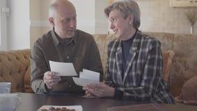 Viejos pares, hombre feliz y mujer mayores sentándose en el sofá, fotografías hablando, riendo y mirando, recordando pasado almacen de video