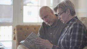 Viejos pares, hombre y mujer, sentándose en el sofá con un libro y hablando y sonriendo el uno al otro Relaciones de familia almacen de video