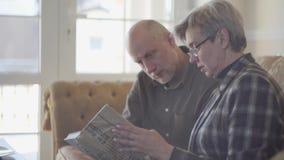 Viejos pares, hombre y mujer, sent?ndose en el sof? con un libro y hablando y sonriendo el uno al otro Relaciones de familia almacen de video