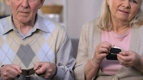Viejos pares infelices que muestran las carteras vacías y que miran inseguridad social de la cámara metrajes