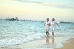 Viejos pares que corren en la playa del mar Fotos de archivo libres de regalías