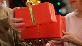 Viejos pares que intercambian las cajas de regalo en la Navidad, sorpresa agradable por días de fiesta almacen de metraje de vídeo
