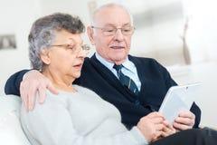 Viejos pares que miran la cámara con PC de la tableta en sus manos imagen de archivo libre de regalías