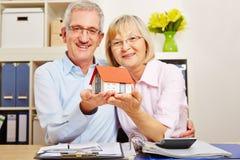 Viejos pares que sostienen la casa en sus manos Imagen de archivo libre de regalías