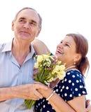 Viejos pares que sostienen la flor Foto de archivo