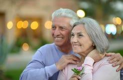Viejos pares sonrientes con las flores Fotografía de archivo