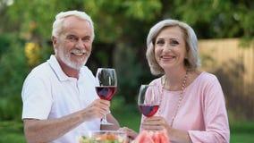 Viejos pares sonrientes que celebran el aniversario con las copas de vino, tradiciones de la familia almacen de video