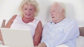 Viejos pares usando un ordenador portátil y un discurso metrajes