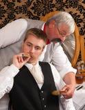 Viejos peluquero y cliente Foto de archivo libre de regalías