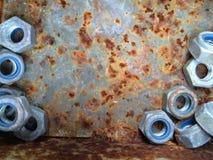 Viejos pernos oxidados, acero, nueces en fondo fotografía de archivo libre de regalías
