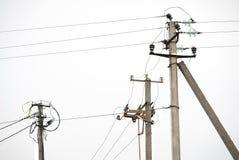 Viejos posts de la electricidad tres Fotos de archivo libres de regalías