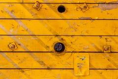 Viejos tableros de madera pintados amarillo con los agujeros Textura de madera natural abstraiga el fondo Fotografía de archivo