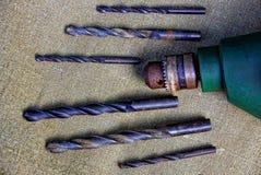 Viejos taladro eléctrico y taladros en un pedazo de paño Imagen de archivo libre de regalías