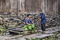 Viejos y más jovenes granjeros que hablan cerca de vertiente de madera Foto de archivo libre de regalías