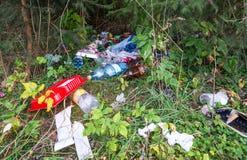 Viel Abfall im Kiefernwald, menschliche Nachlässigkeit stockfotografie