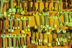 Viel befestigt lange silberne leere Weinlese das Hängen an einer Schraube an einem hölzernen braunen Brett in der Werkstatt Lizenzfreies Stockbild