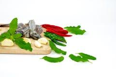 Viel Garnele auf einem hölzernen hackenden Brett um frische Paprikas und Basilikumblätter lizenzfreie stockfotos
