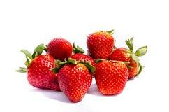 Viel großes rotes Erdbeere-` s mit den darstellenden Samen und den grünen Oberteilen Lizenzfreies Stockfoto