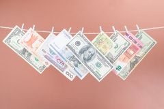 Viel h?ngt Dollarscheine an einem Seil mit der h?lzernen W?scheklammer, die auf braunem Hintergrund lokalisiert wird stockfoto