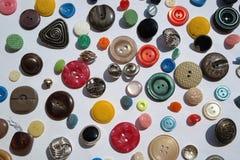 Viel helle farbige Vielzahl von runden Knöpfen, verschiedene Beschaffenheiten, Durchmesser, auf einem weißen Hintergrund Stockbild